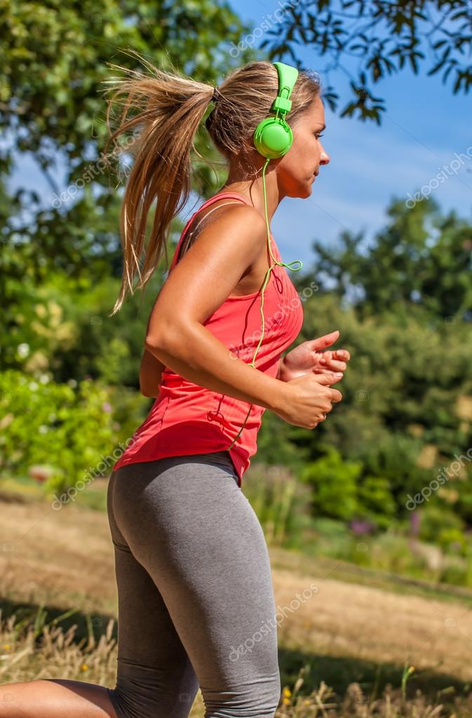 profile of trendy young blond woman running with music on