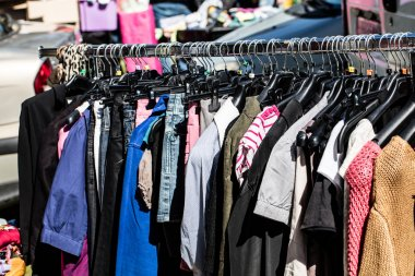 various fast fashion female clothes on rack at street fair
