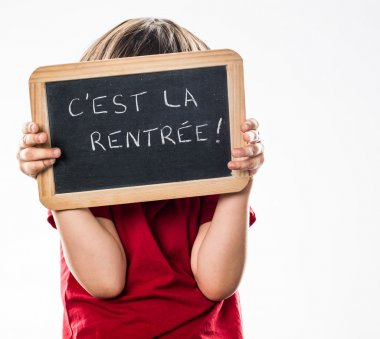 anonymous shy little kid protecting oneself behind French writing slate