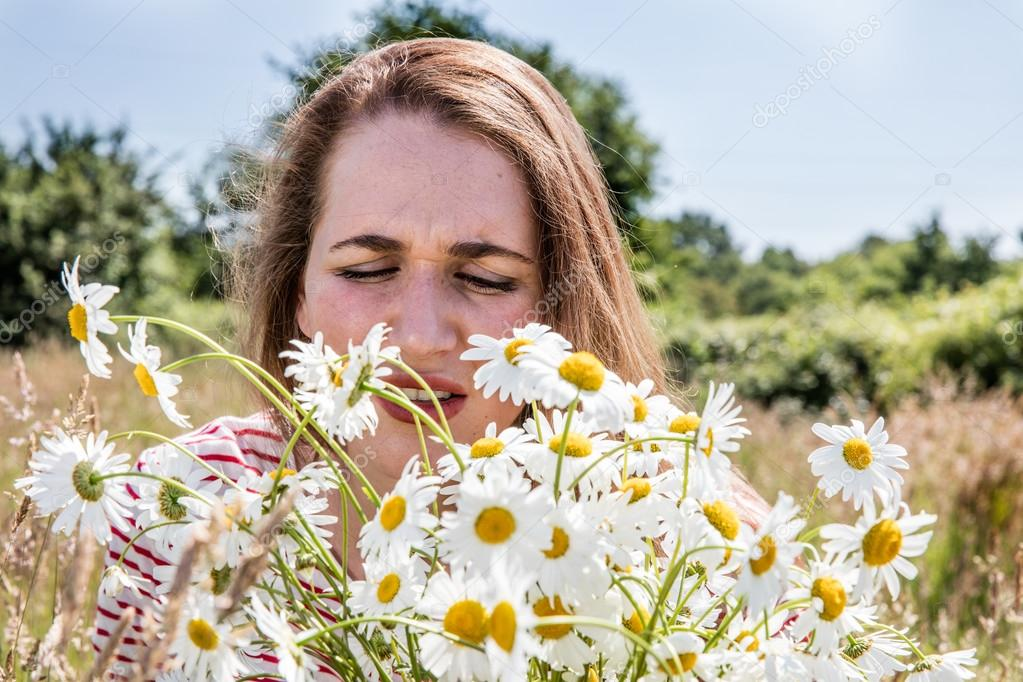 sneezing girl with allergies or hay fever smelling daisy flowers