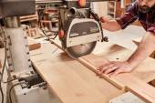 Fotografie carpenter cutting piece of wood with saw