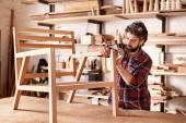 Photo artisan carefully sanding chair frame