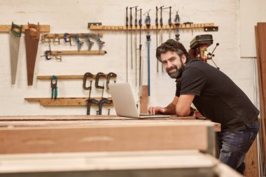 designer working on laptop on workbench in studio