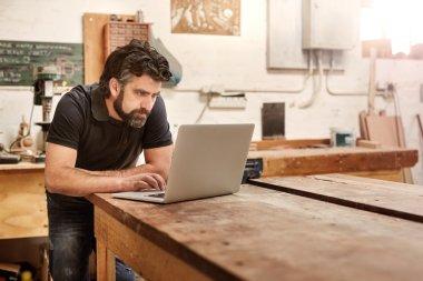 Designer working on laptop on workbench in studio