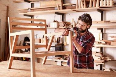 artisan carefully sanding chair frame