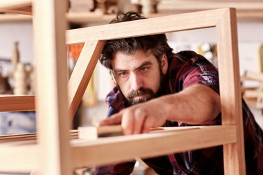 artisan carefully sanding chair frame