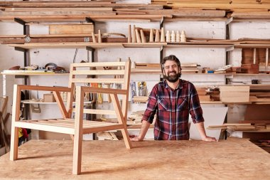 craftsman in woodwork studio with wooden chair