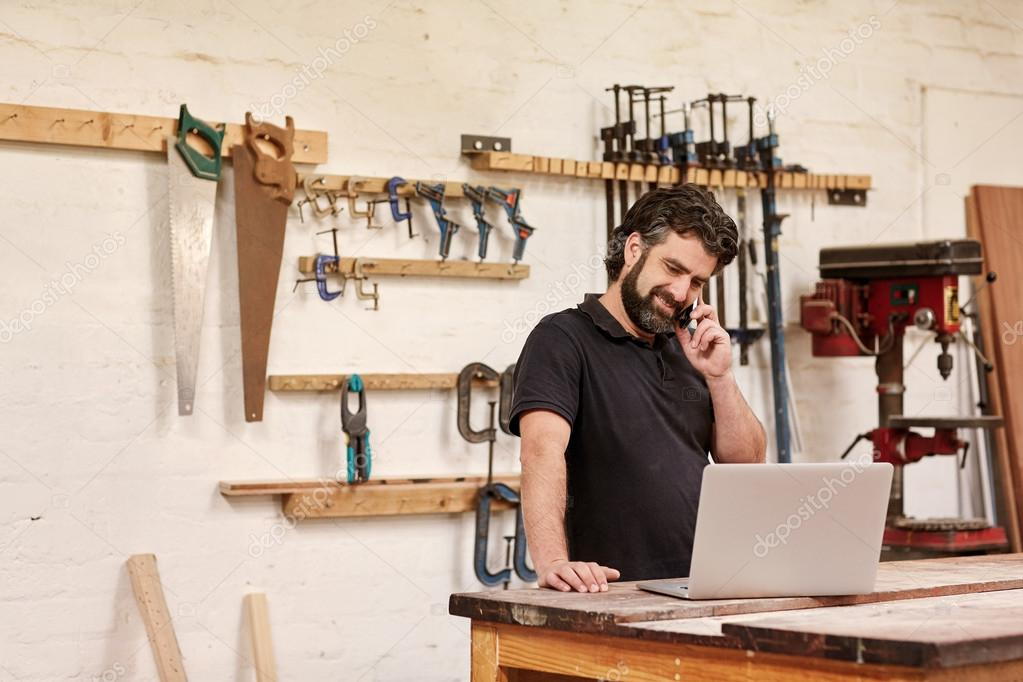 craftsman talking on phone and looking at laptop