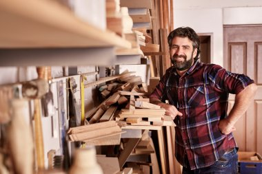 carpenter standing confidently in workshop