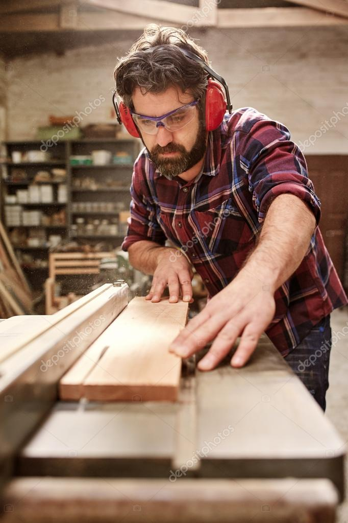 Carpenter cutting wooden plank with saw