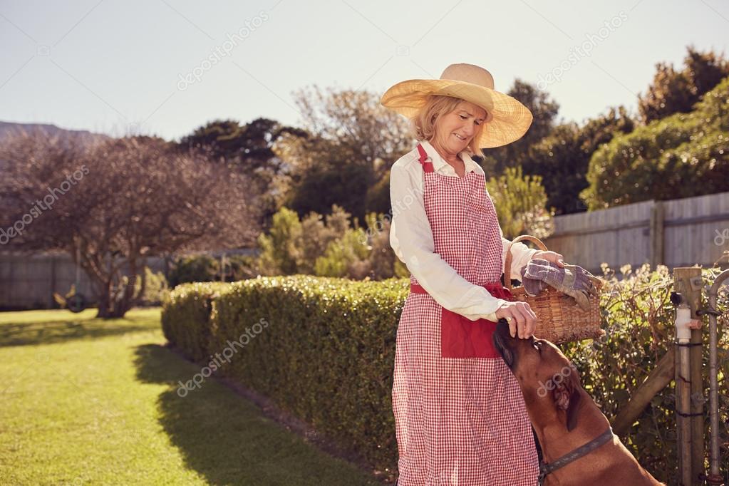 senior woman greeting dog in backyard