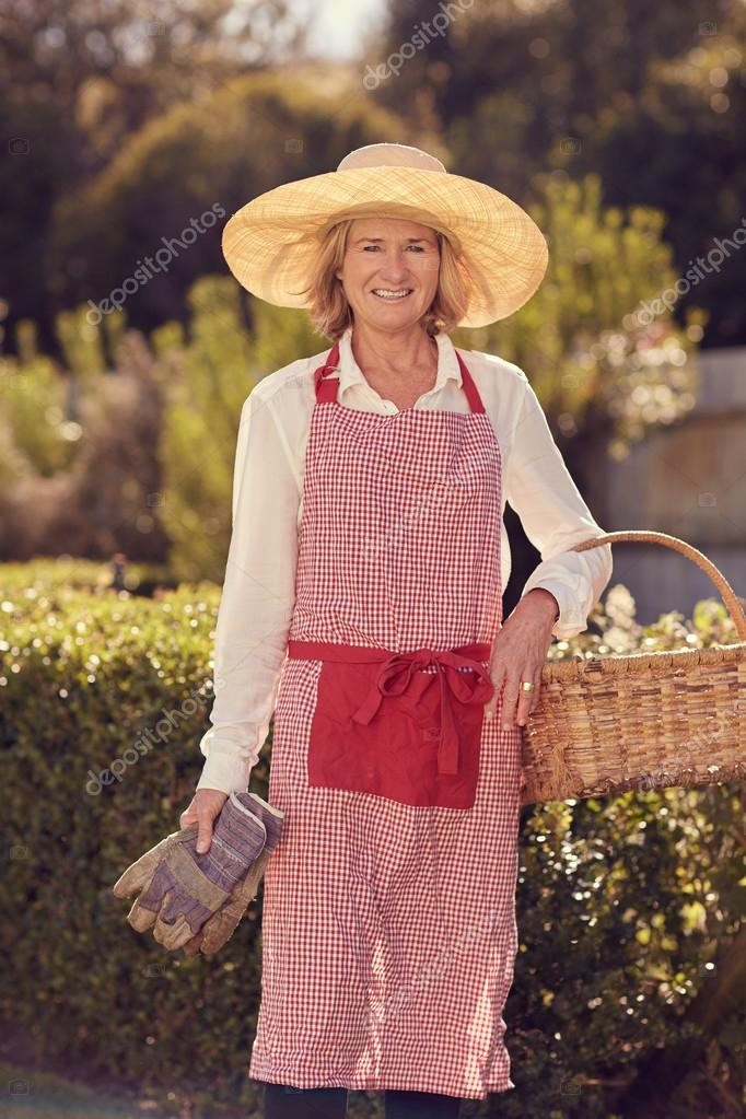 woman holding basket and gardening gloves