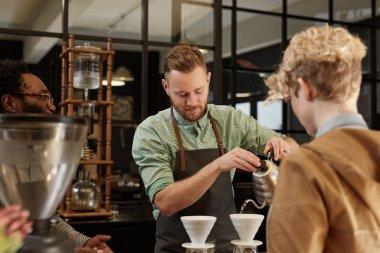 Barista pouring coffee through filter