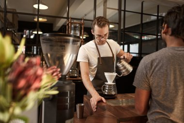 Barista pouring coffee in modern cafe