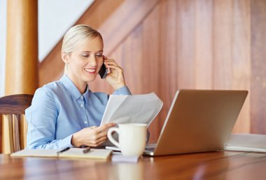 businesswoman talking on phone checking documents