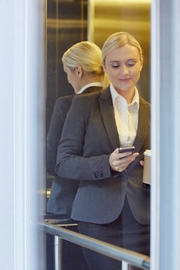 businesswoman texting someone in elevator