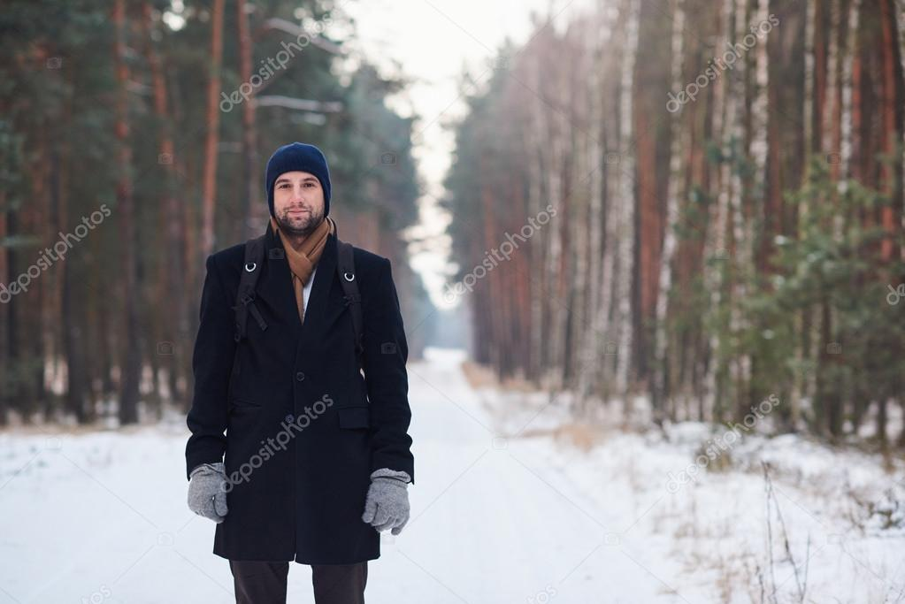 man standing on road in forest