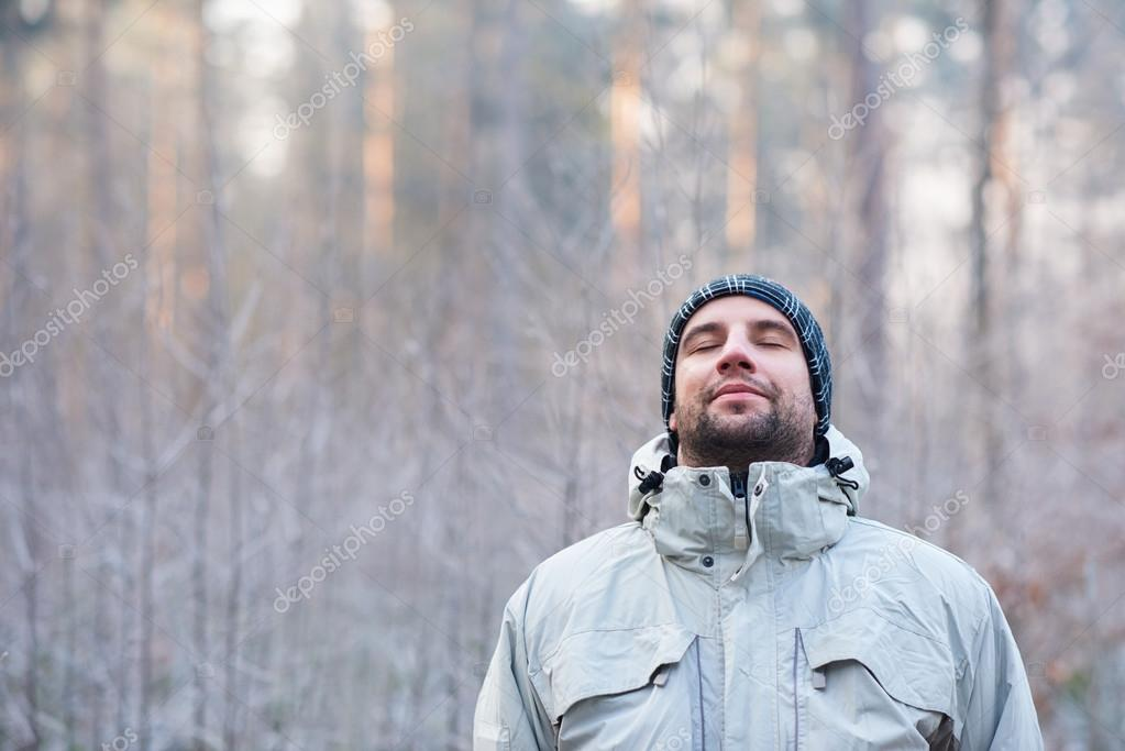 man breathing deeply in winter forest