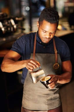 barista pouring frothed milk in cappuccino