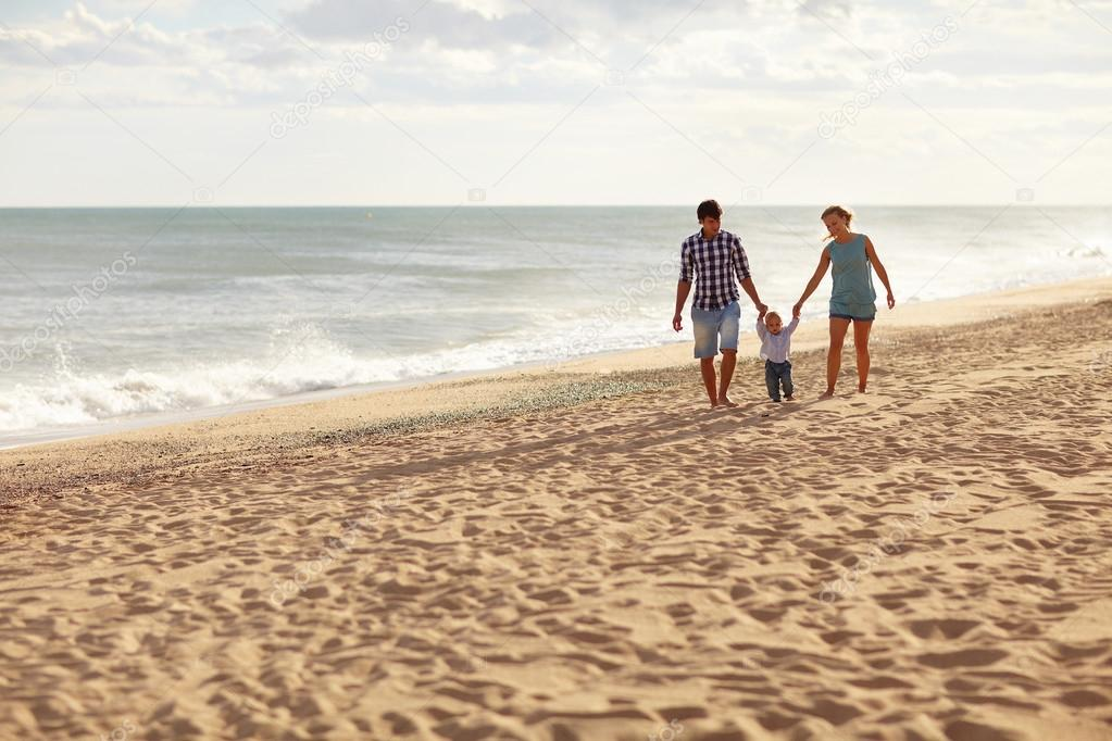 Family walking together on quiet beach