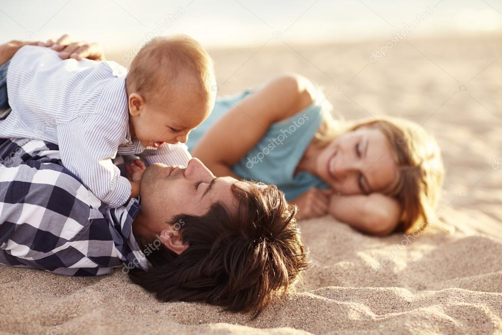 Baby boy laughing while playing with dad