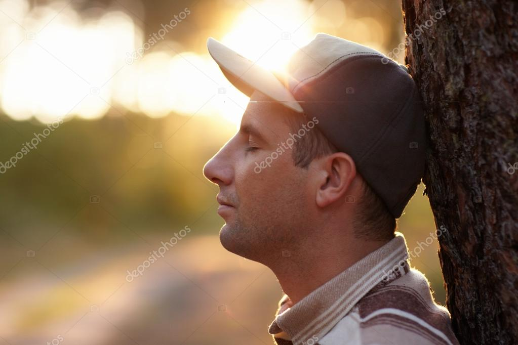 man looking away meditatively in forest