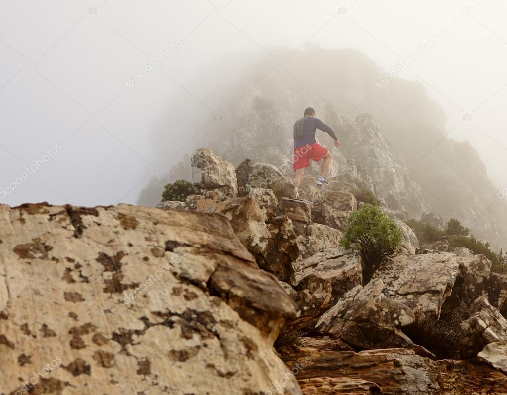 man hiking up to top of mountain