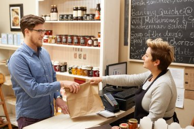 deli employee handing brown bag