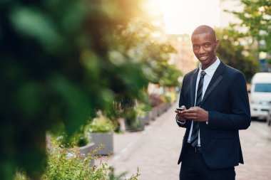 businessman standing in city and holding phone