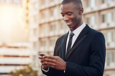businessman looking at mobile phone in city
