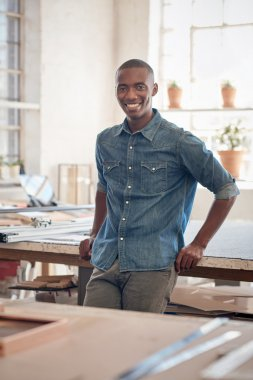 business owner leaning on work bench