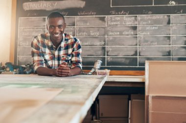 business owner leaning on work table