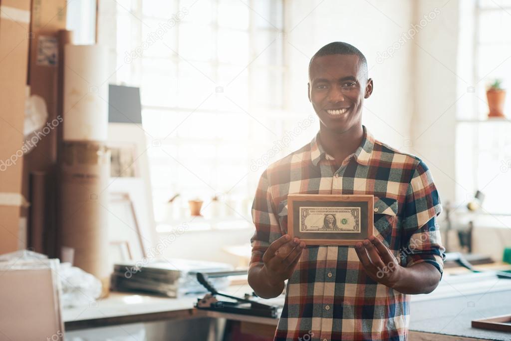 business owner holding framed dollar bill ストック写真