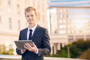 businessman using digital tablet with city