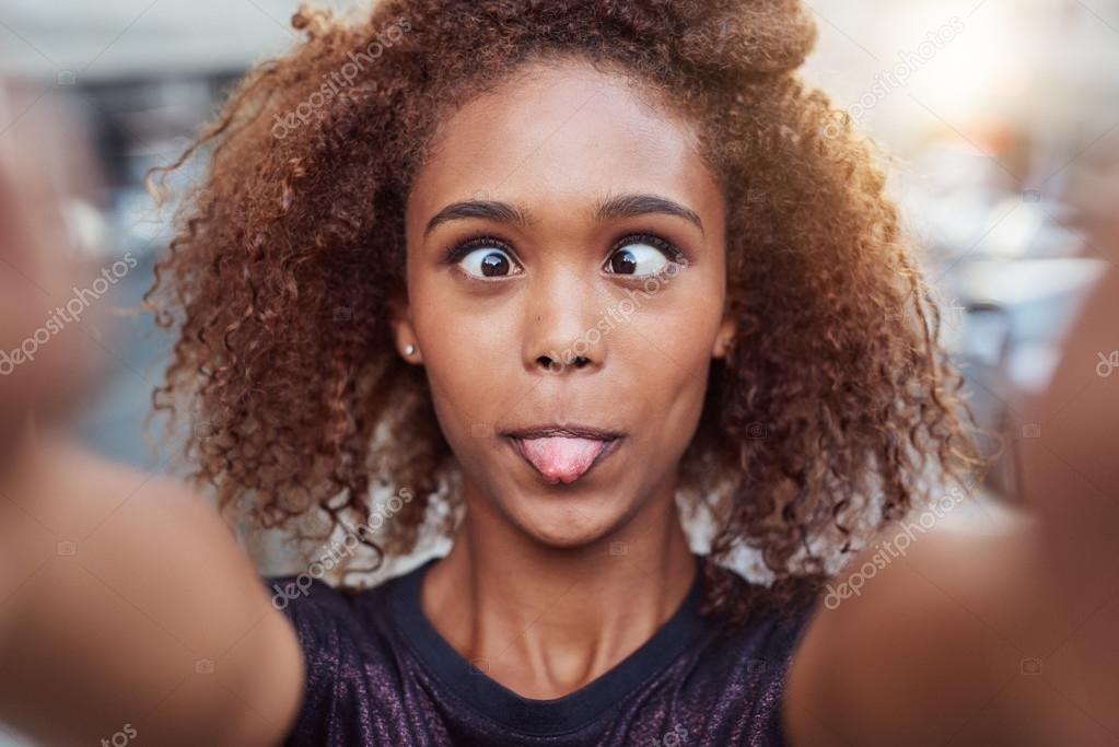 Woman making silly face while taking selfie
