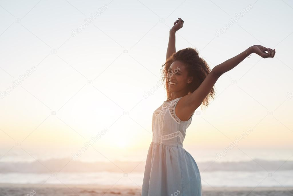 woman standing on beach with arms raised
