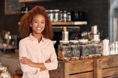 woman standing with arms crossed in cafe