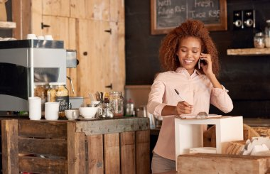 woman talking on phone while working in cafe