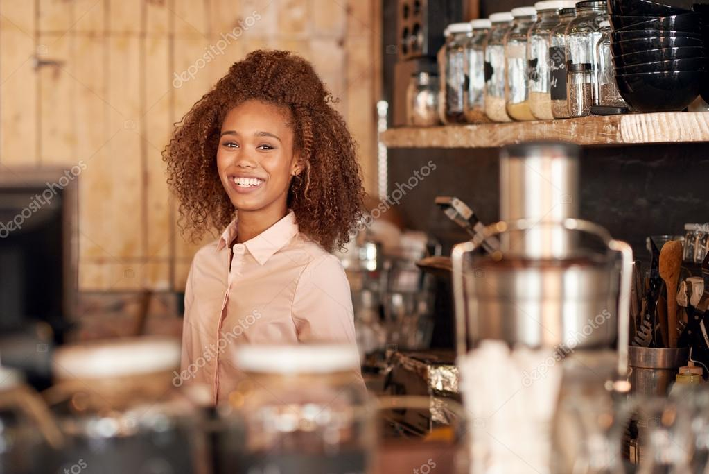 Woman standing behind counter of cafe