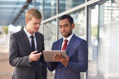 businessmen talking together over digital tablet