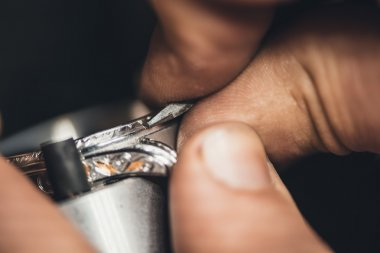 jeweler using tools to shape ring