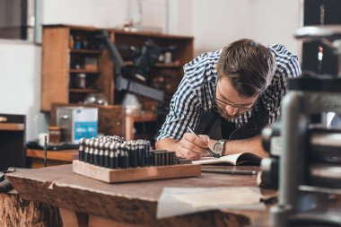 Jeweler sketching out jewelry designs in notebook