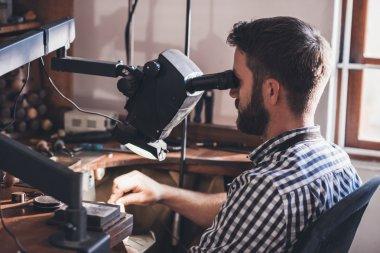 Jeweler looking through large magnifier