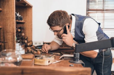 jeweler examining ring and talking on cellphone