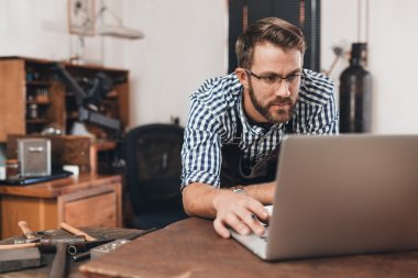 jeweler working on laptop while leaning on bench
