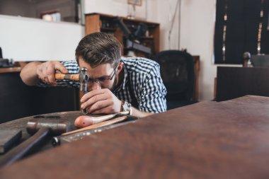 jeweler using hammer to shape ring