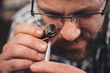 jeweler using loupe to examine diamond