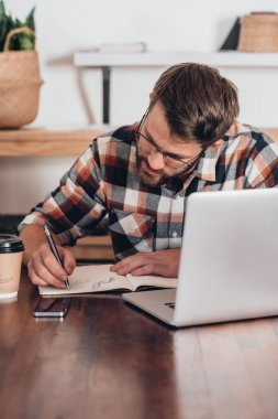 entrepreneur writing in notebook next to laptop