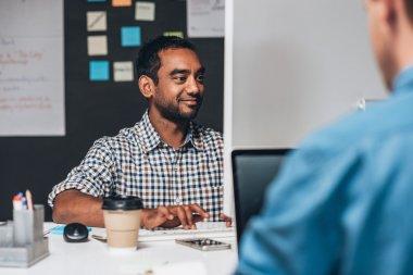 designer sitting at desk working on computer