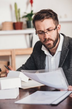 entrepreneur reading paperwork and preparing packages